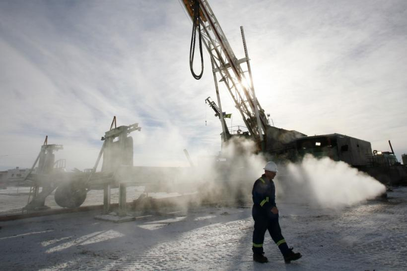 Doug Shea, drill informant for EnCana, walks past an EnCana gas drilling well east of Calgary, Alberta, February 15, 2007.