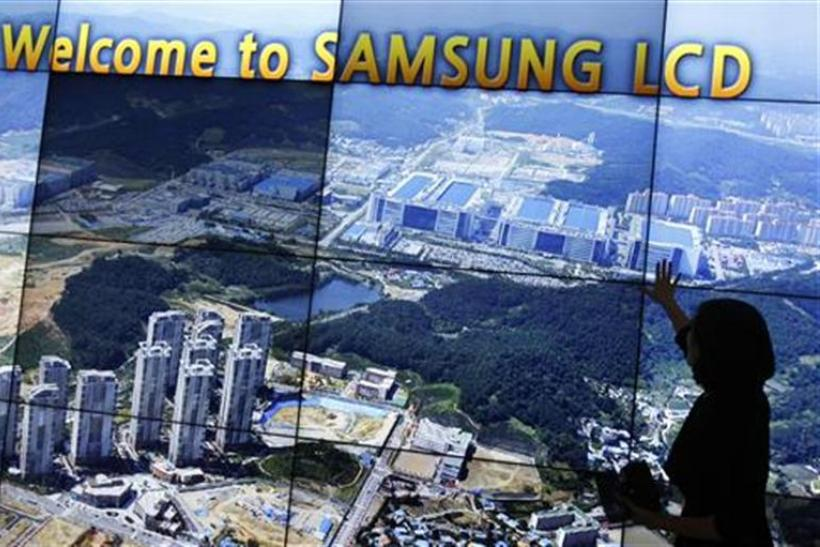 An employee of Samsung Electronics explains as a monitor shows the company's main factory at its showroom in Asan