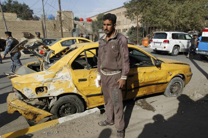 A man stands near his damaged vehicle after a bomb attack in Baghdad's Karrada district