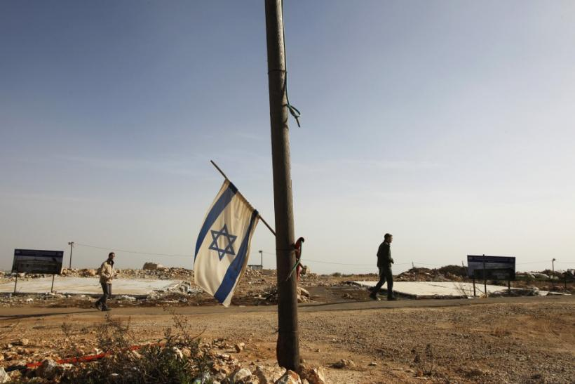 An Israeli flag hangs off a pole in front of two foundations of temporary homes demolished by the Israeli authorities last year in the unauthorised Jewish outpost of Migron, near the West Bank city of Ramallah February 8, 2012.