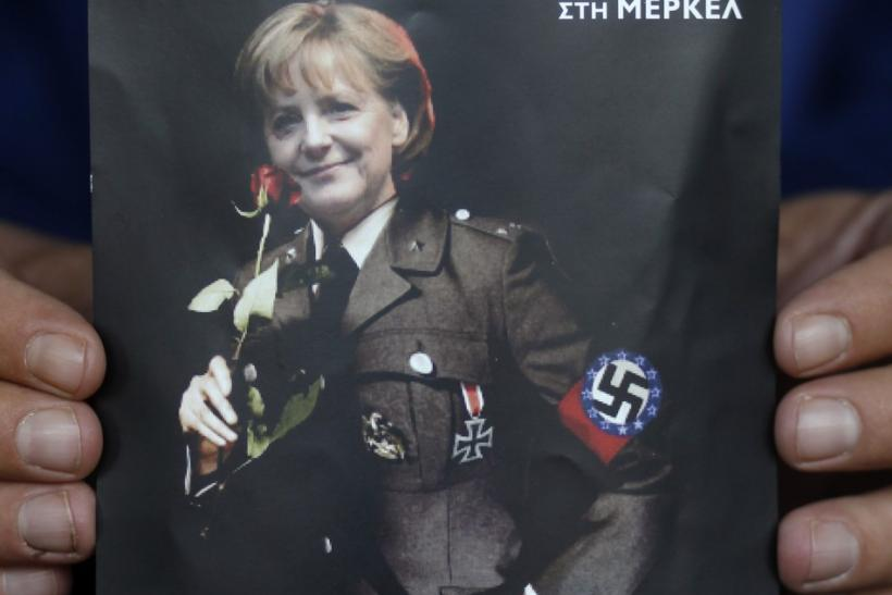 A man displays a poster depicting German Chancellor Merkel in a Nazi uniform in Athens