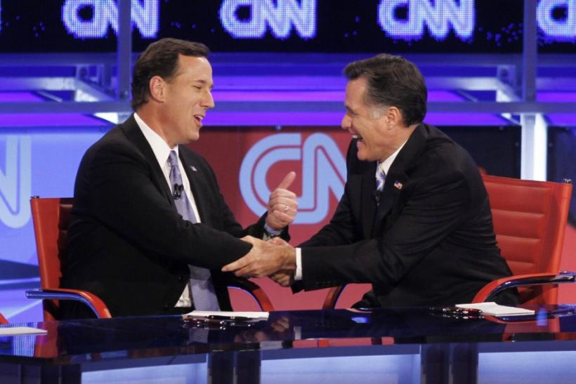 U.S. Republican presidential candidates, former U.S. Senator Rick Santorum and former Massachusetts Governor Mitt Romney (R) laugh as they shake hands at the conclusion of the Republican presidential candidates debate in Mesa, Arizona, Feb. 22, 2012.