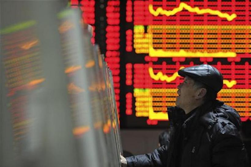 An investor checks stock information with a computer at a brokerage house in Hefei
