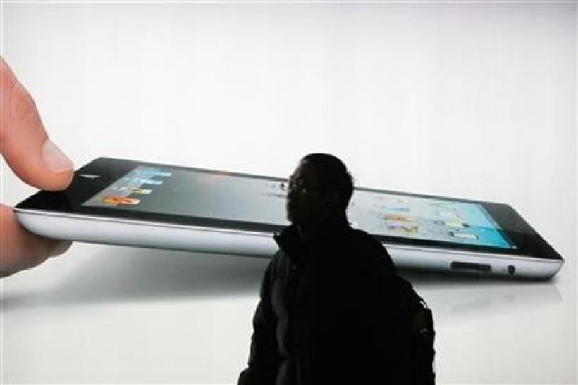 A man walks past an iPad 2 advertisement in Shanghai February 21, 2012.