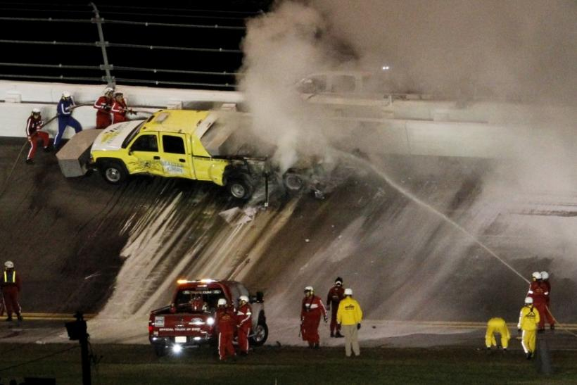 Firefighters battle flames which erupted from a jet dryer after it was hit by Juan Pablo Montoya of Colombia in his number 42 Chevrolet during the NASCAR Sprint Cup Series 54th Daytona 500 race at the Daytona International Speedway in Daytona Beach