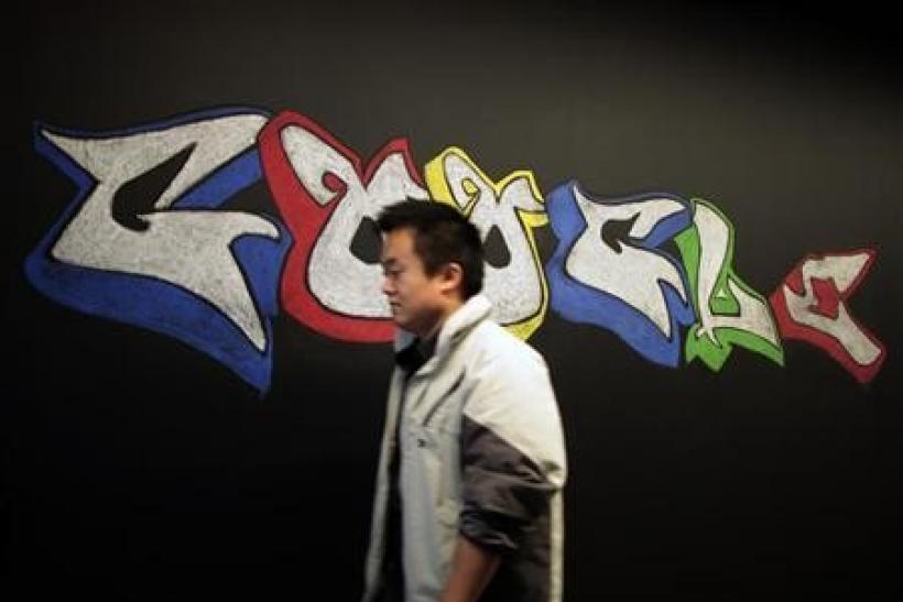 A man walks past a Google logo drawn with chalk on a wall at the Google campus near Venice Beach, in Los Angeles, California January 13, 2012.