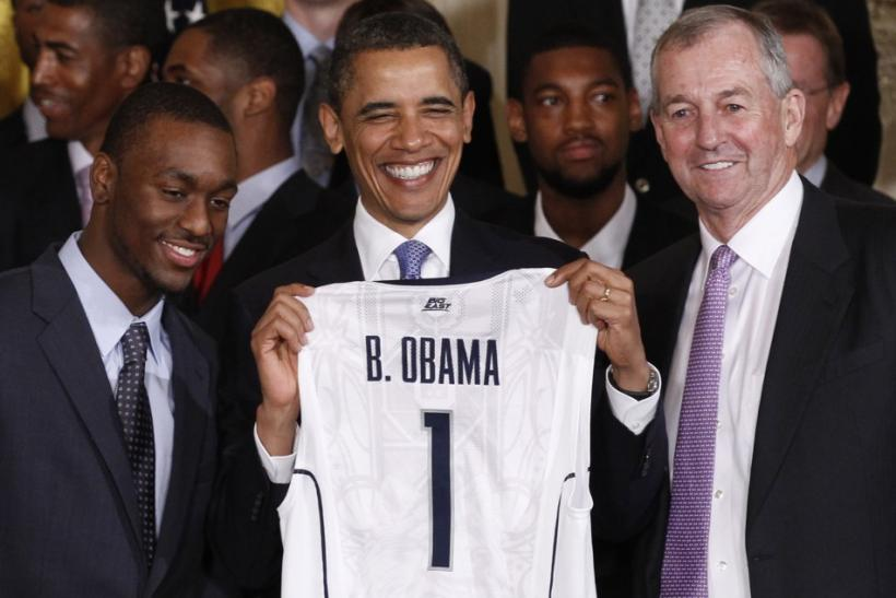 The Connecticut men's basketball team presents Barack Obama with a jersey as they visit the While House after winning the national championship.