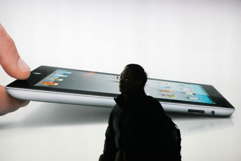 A man walks past an iPad 2 advertisement in Shanghai
