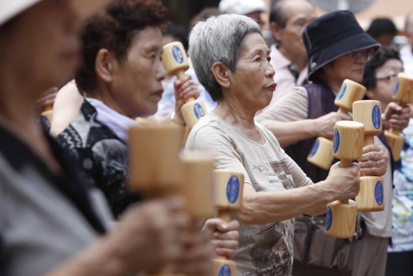 """Women exercise with wooden dumbbells during a health promotion event to mark Japan's """"Respect for the Aged Day"""" at a temple in Tokyo"""