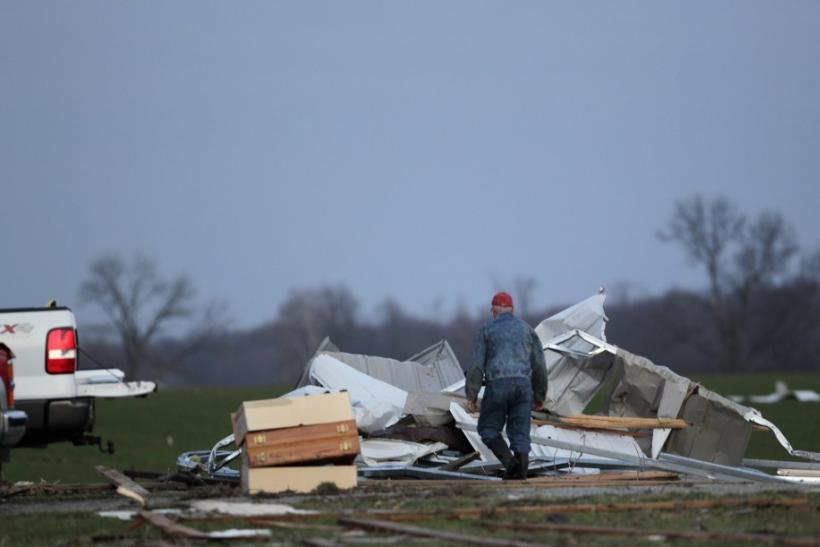 A resident works to clear storm damage after three tornadoes moved through the area in Chelsea, Indiana