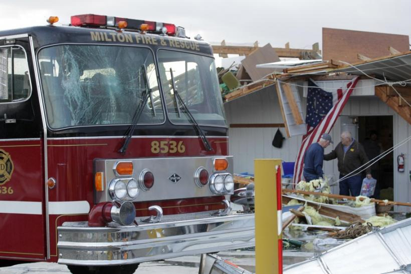 Members of the Milton Fire department work to clear storm damage after a tornado hit the fire house in Milton