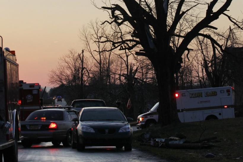 Local emergency workers help residents clear storm damage after three tornadoes moved through the area in Chelsea