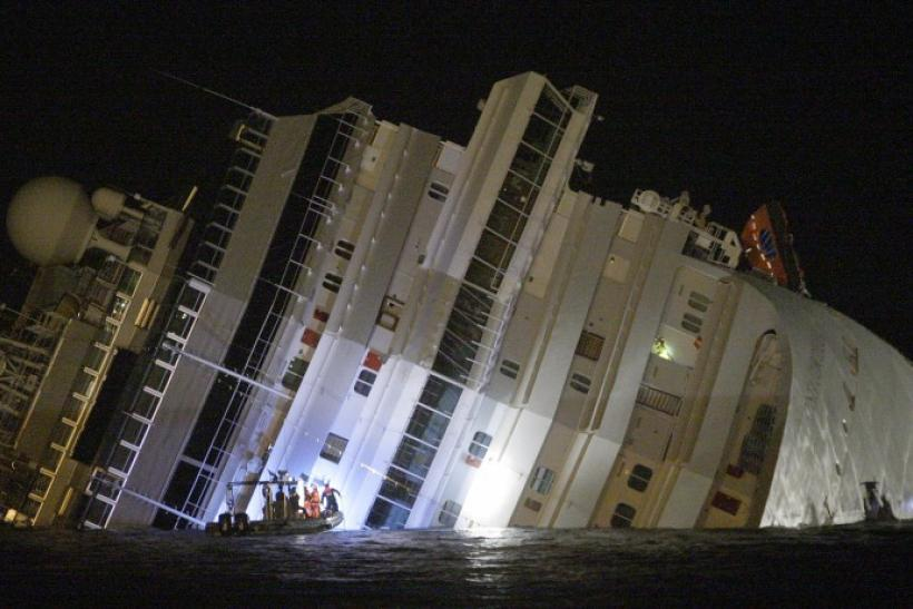 Rescuers are seen next Costa Concordia cruise ship that ran aground off the west coast of Italy at Giglio island January 14, 2012.