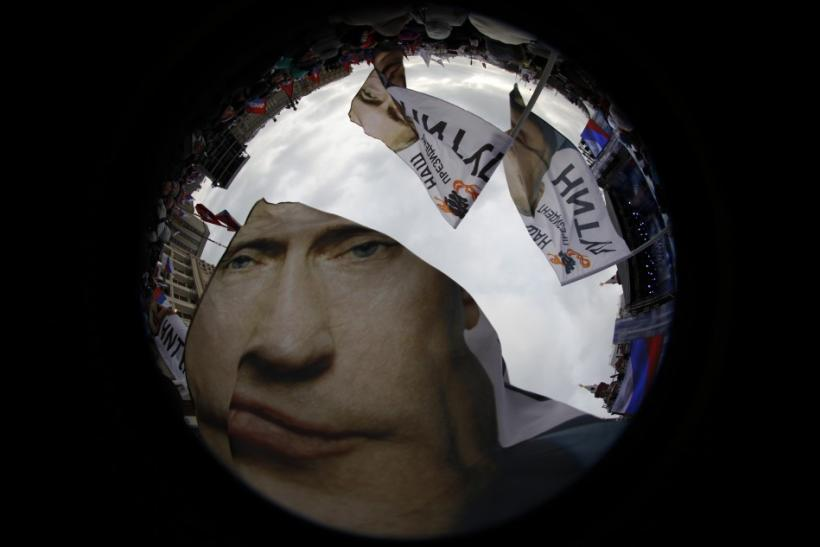 Supporters of Vladimir Putin wave flags in a picture taken with a fisheye lens before a rally in central Moscow.