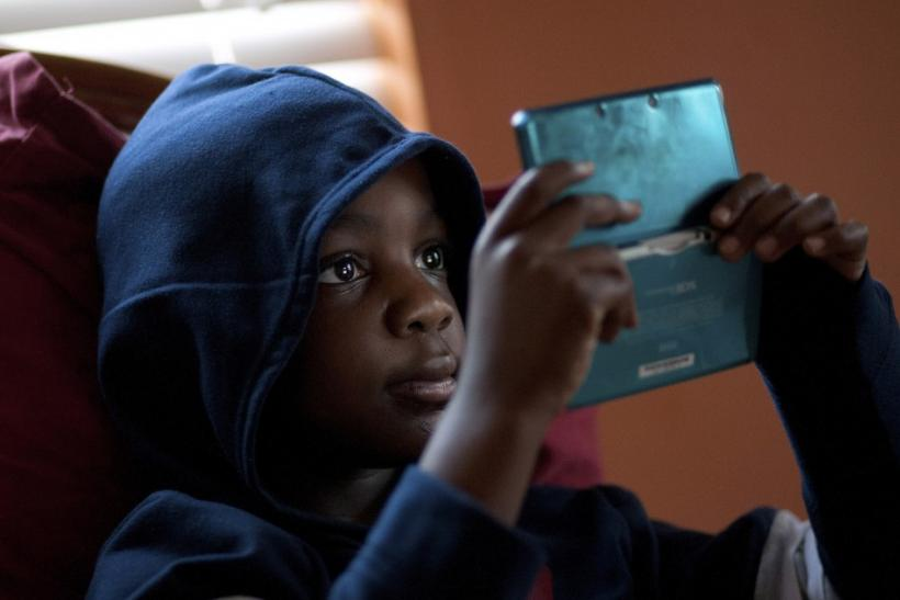 Jamal Stevens, 7, plays a video game at his grandparent's home in Charlotte.