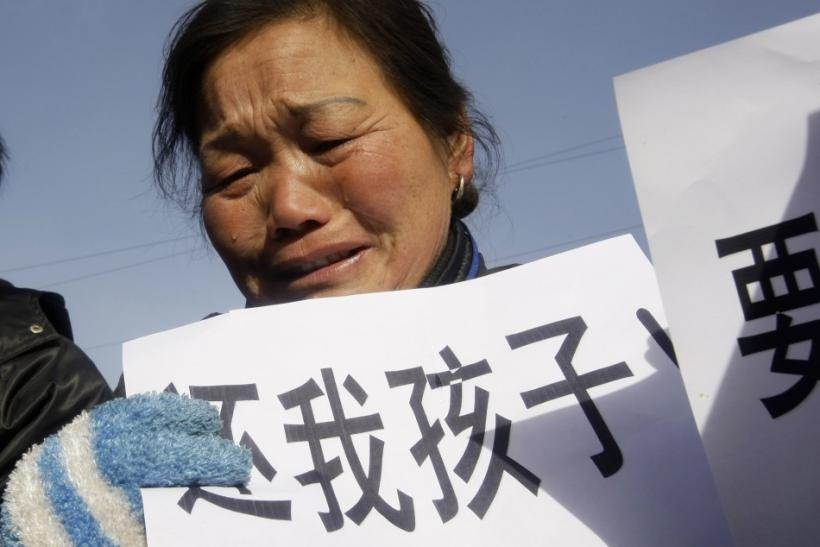 A woman, whose child died from drinking tainted milk, holds a sign outside Shijiazhuang Intermediate People's Court