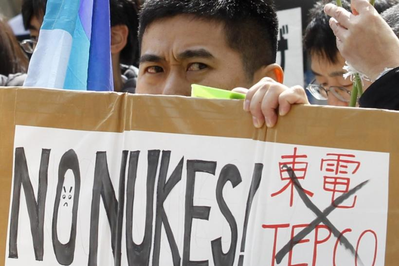 An anti-nuclear protester holds a placard during a rally in front of the headquarters of Tokyo Electric Power Co. (TEPCO), operator of the tsunami-crippled Fukushima Daiichi nuclear power plant, in Tokyo March 11, 2012, to mark the first anniversary of th