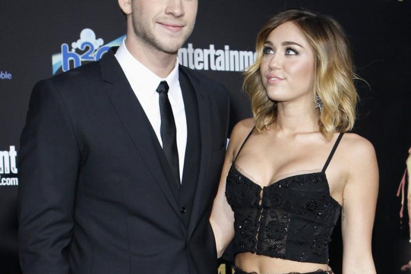 "Cast member Liam Hemsworth poses with actress Miley Cyrus at the premiere of ""The Hunger Games"" at Nokia theatre in Los Angeles"