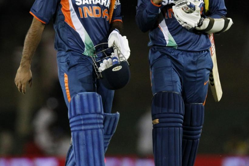 India's Sehwag and captain Dhoni share a laugh as they walk off field after their team's victory.