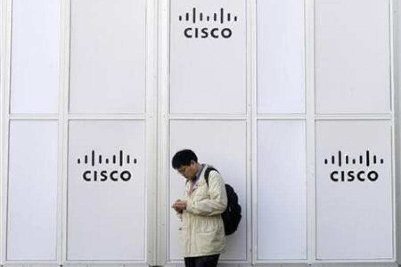 A man looks at his mobile next to a Cisco banner at the Mobile World Congress in Barcelona February 17, 2010.
