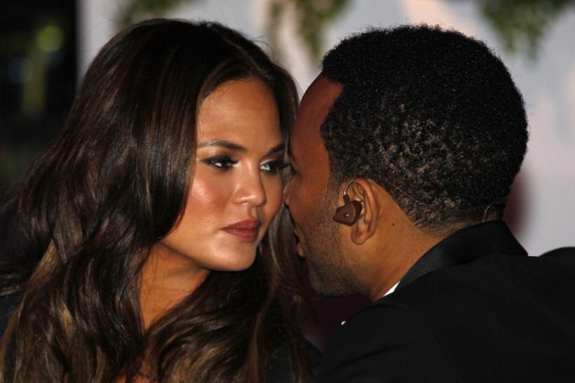 Singer John Legend and his girlfriend Chrissy Teigen kiss at the State Dinner held to honor British Prime Minister David Cameron at the White House in Washington March 14, 2012.