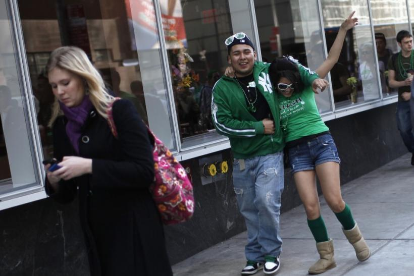 A man helps a woman down the sidewalk as they celebrate along 5th Avenue in New York during the city's 250th annual St. Patrick's Day parade, March 17, 2011.