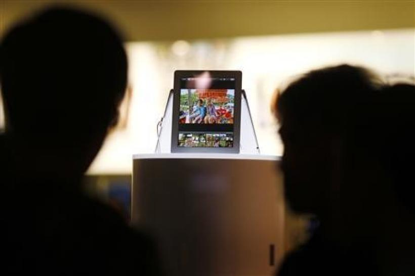 Passers-by look at a new iPad in a window display in an Apple store in Sydney March 15, 2012.