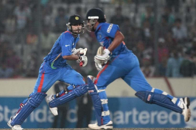 India's Dhoni and Kohli run between the wickets against Pakistan during their Asia Cup One Day International cricket match in Dhaka