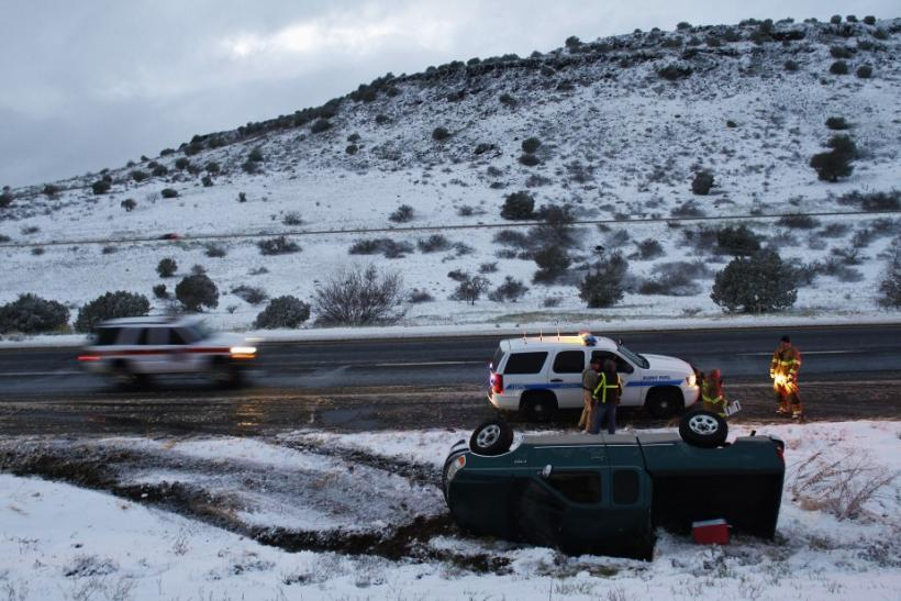 Firefighters and police officers stand near a pick-up truck that rolled on its side after the driver lost control along Interstate-17 in Yavapai County, Arizona, March 18, 2012. The late winter storm kept temperatures well below normal in California on Su