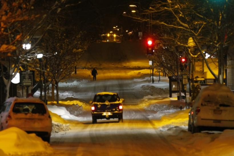 A pedestrian walks along San Francisco Street as several inches of snow cover the ground in Flagstaff, Arizona March,18 2012. The late winter storm kept temperatures well below normal in California on Sunday and generated heavy snow fall in several states