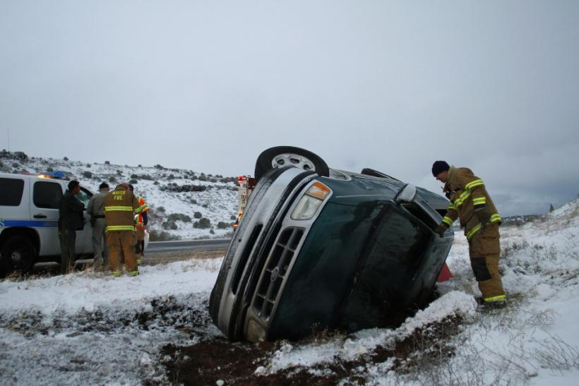 A firefighter looks into the passenger side of a pick-up truck that rolled on its side after the driver lost control along Interstate-17 in Yavapai County, Arizona March 18, 2012. The late winter storm kept temperatures well below normal in California on