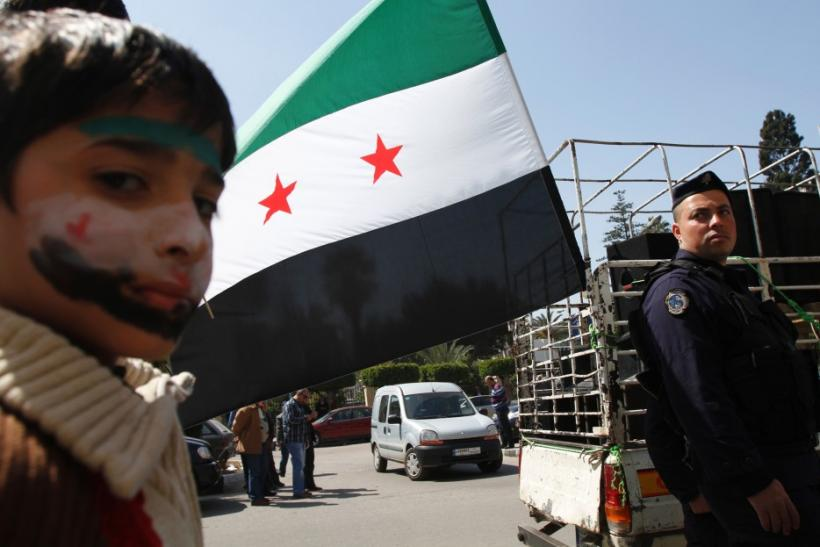A refugee who recently fled from Syria attends a demonstration in solidarity with Syrians against the regime, in Tripoli
