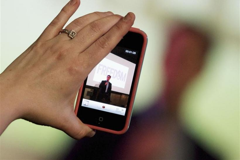 A woman takes a video with her iPhone as Republican presidential candidate and former U.S. Senator Rick Santorum addresses supporters at a Get Out The Vote rally in Mandeville, Louisiana March 21, 2012.