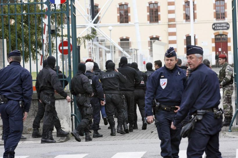 Masked French special unit policemen leave after the assault to capture gunman Mohamed Merah during a raid on a five-storey building in Toulouse