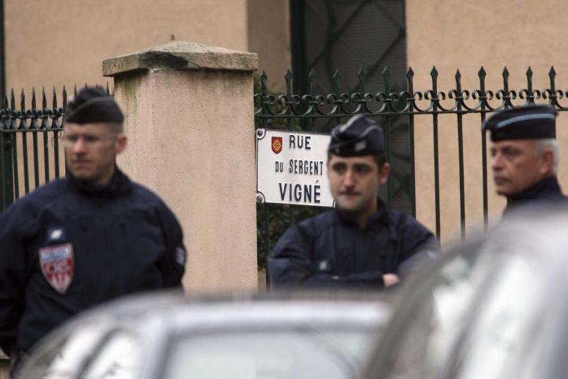 French CRS police secure a street during a raid on a house to arrest suspect in the killings of three children and a rabbi on Monday at a Jewish school, in Toulouse