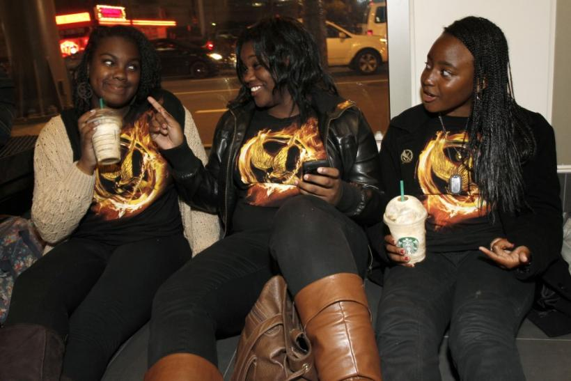 "(L - R)Fans Tori Rogers, Lawreca Jones, and Serene Gord wear ""The Hunger Games"" t-shirts as they wait in line for the midnight screening of the movie during opening night at Regal Cinemas in Los Angeles, California March 22, 2012."