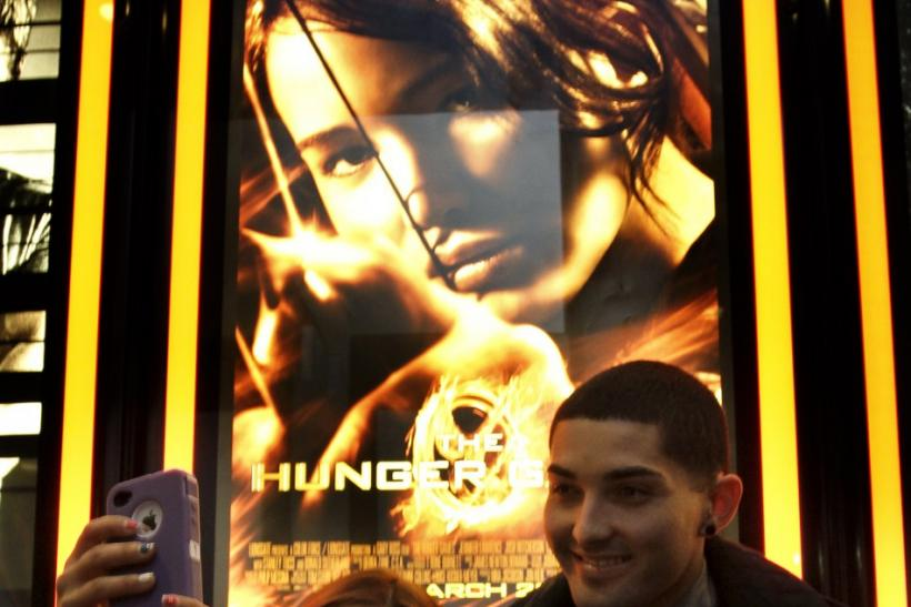 "Elizabeth Arellano and Sal Arellano pose for a photo in front of a movie poster of ""The Hunger Games"" at Regal Cinemas in Los Angeles, California March 22, 2012."