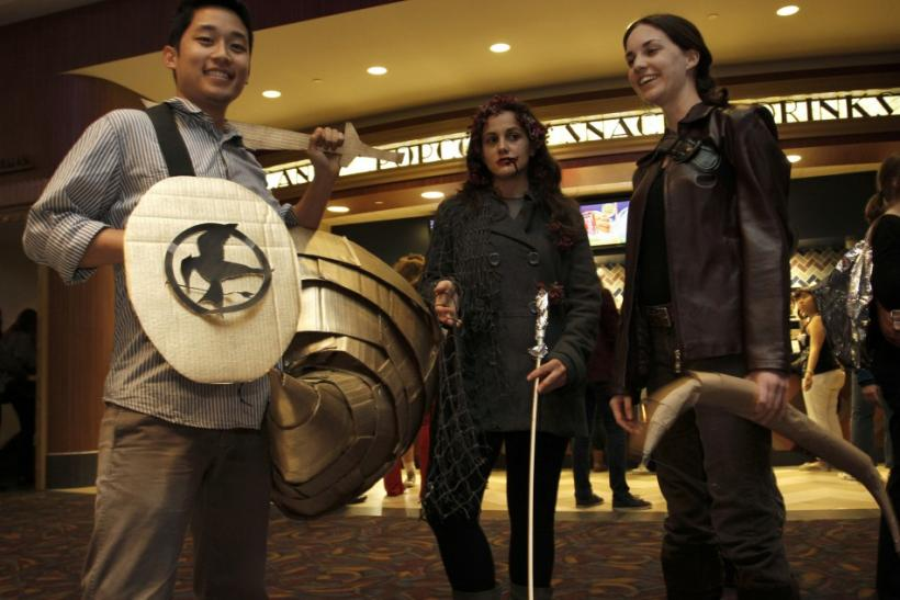 "(L - R)Fans Kyle Apuna, Sierra Betinis and Amanda Hearle dressed up as characters from ""The Hunger Games"" pose on the opening night at Regal Cinemas in Los Angeles, California March 22, 2012."