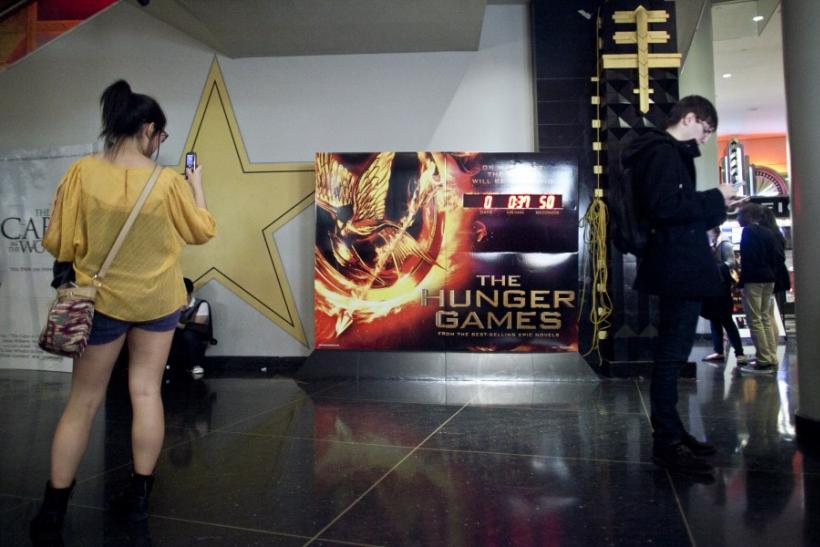 "Movie-goers stand near a clock counting down the time till the midnight showing of ""The Hunger Games"" at the AMC Loews Lincoln Square Theatre in New York March 22, 2012. The film is based on the popular young adult book series by Suzanne Collins"