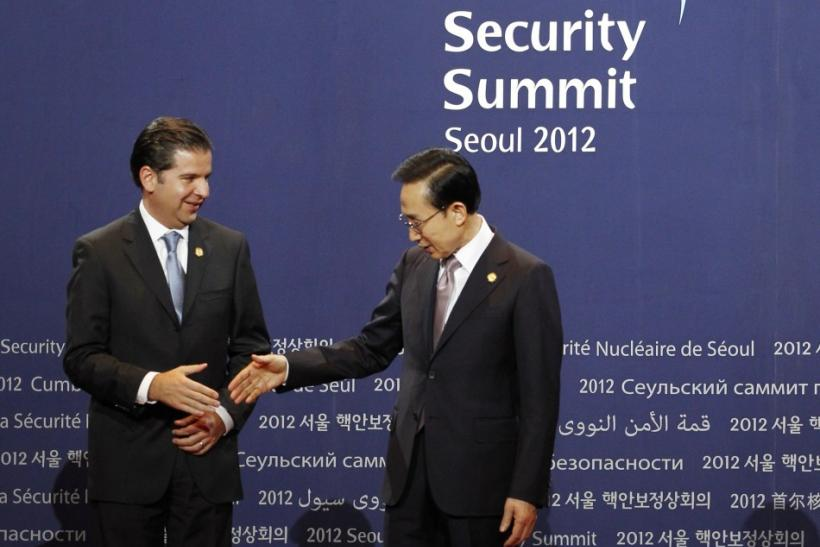 South Korea's President Lee reaches out to shake the hand of Mexico's Energy Minister Herrera at the Nuclear Security Summit working dinner in Seoul