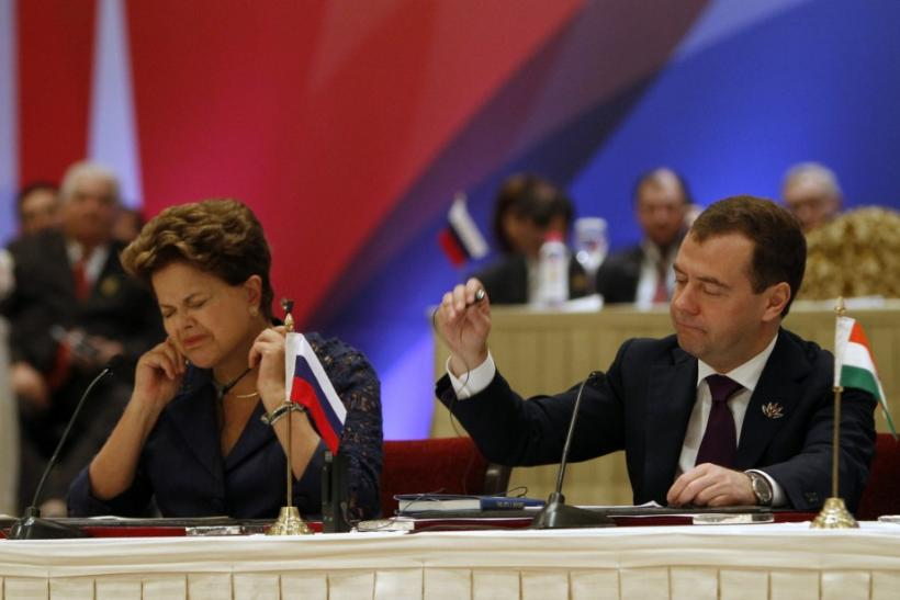 Brazil's President Rousseff and Russian President Medvedev adjust their microphones at the end of the plenary session of the BRICS Summit in New Delhi