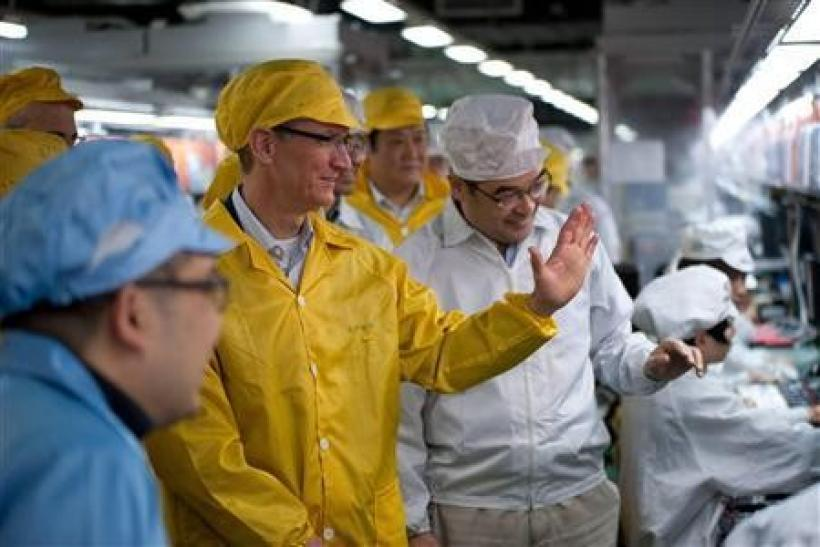 Apple Chief Executive Officer Tim Cook (2nd L) talks to employees as he visits the iPhone production line at the newly built Foxconn Zhengzhou Technology Park, Henan province in this March 28, 2012 handout photo.