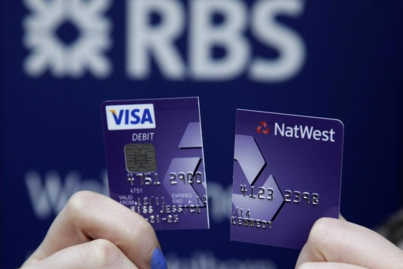 A demonstrator holds up her destroyed NatWest debit card as she stands in front of a branch of the Royal Bank of Scotland in London