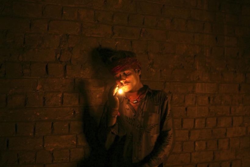 A labourer smokes as he takes a break inside a steel factory on the outskirts of Jammu March 15, 2012.