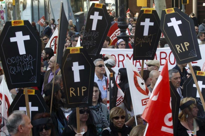 Protesters carry cardboard coffins that signify the death of decent employment, wages and public health in central Barcelona during a general strike in Spain