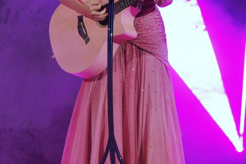 Singer Katy Perry performs with a guitar at the 2011 American Music Awards in Los Angeles