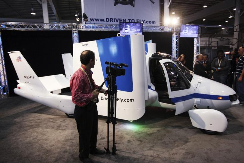 A man films aircraft company Terrafugia's flying car, called the Transition, at the 2012 International Auto Show in New York