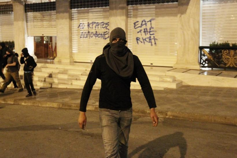 A protester walks away from the entrance of Grande Bretagne hotel during riots at central Syntagma square in Athens