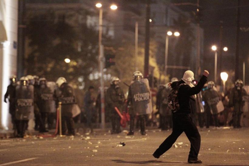A protester throws a stone at policemen during riots at central Syntagma square in Athens