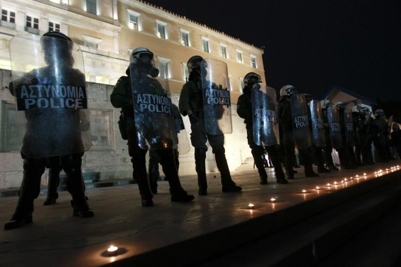 Candles commemorating the death of a pensioner are placed in front of the parliament in Athens